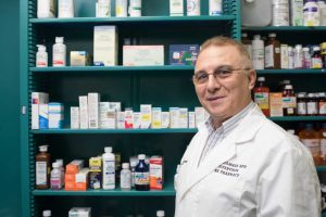 Pharmacist Standing In Front Of Prescriptions